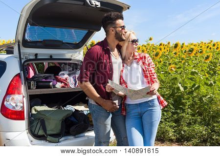 Couple looking road map standing sunflowers field outdoor, mix race man and woman standing near car trunk summer day holiday trip