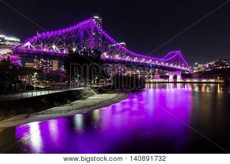 Brisbane Story Bridge (magenta) and beach by night
