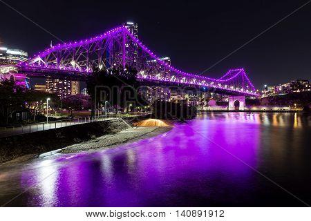 Brisbane Story Bridge by night in magenta with steel wool spinning on beach