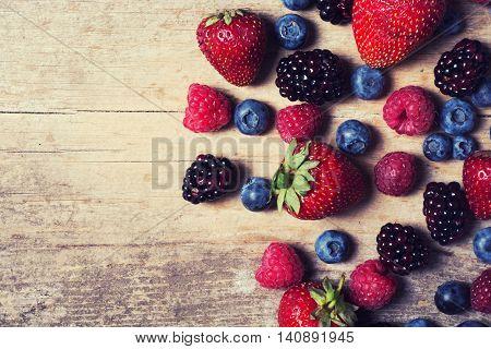 berries : raspberries blueberries blackberries strawberries on a wooden background.