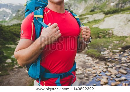 Hiking man portrait with backpack walking in nature. Caucasian man holding hands on backpack, hiking near the river.