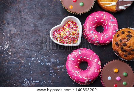Junk, unhealthy food concept. Colorful donuts on a grunge rusty table. Selective focus, copy space background, top view, flat lay