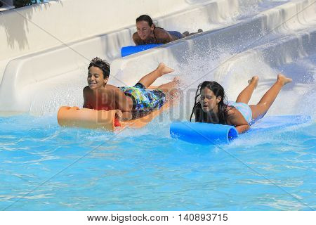 Rhodes Greece-July 30 2016 : Family on the mat racer slide.Mat racer slide is very popular for young people in the Water Park.Water Park is located on the island of Rhodes in Greece and one of the most largest in Europe and is a very popular place