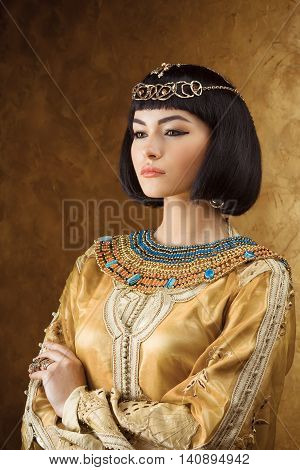 Photo of serious woman with Cleopatra makeup, closeup portrait of beautiful female with stylish haircut, young lady wearing fashionable golden necklace, beauty salon