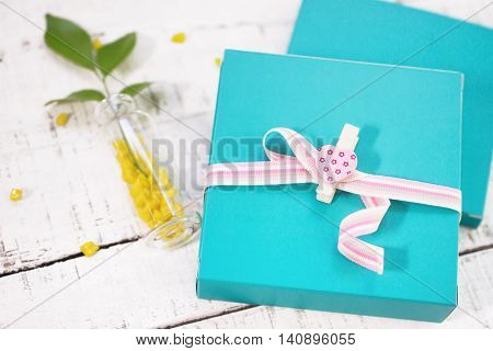 two gift boxes with heart shaped pin and plant in vase on white wood. Valentines day background. love romance concept
