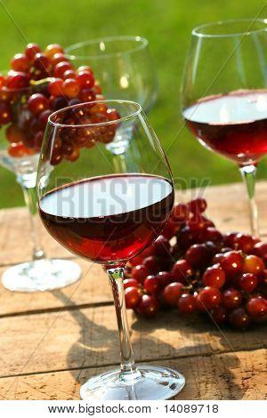 Tres vasos de vino tinto con uvas de mesa rústica