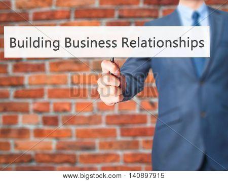 Building Business Relationships - Businessman Hand Holding Sign