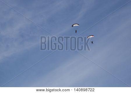 Copenhagen, Denmark - July 30, 2016: Two skydivers just before landing in a lake at the Copenhagen Swoop Challenge.