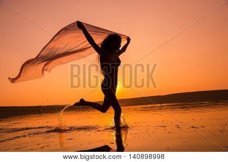 Silhouette of beautiful young girl running on the beach