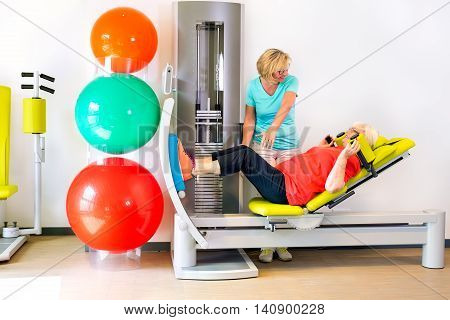 Therapist With Patient Strengthening Legs