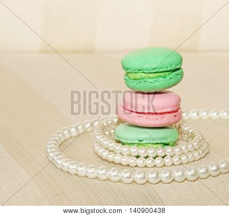 Sweet and colourful french macaroons and pearls on retro-vintage background
