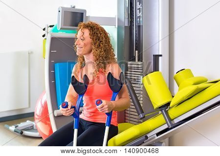 Patient With Crutches Sitting On Weight Machine