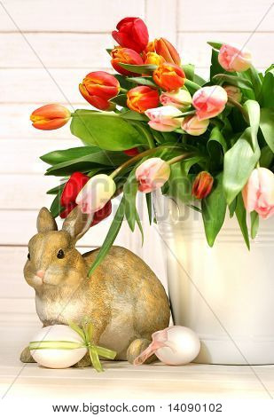 Little rabbit behind white container full of tulips