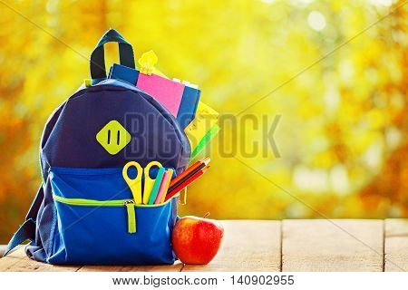 Full School backpack on wooden and autumn nature background.