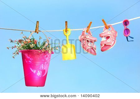 Summer toys and sandals on clothesline against a blue sky