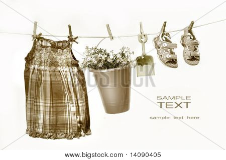 Little girl clothes and toys on a clothesline against white background/ Sepia tone