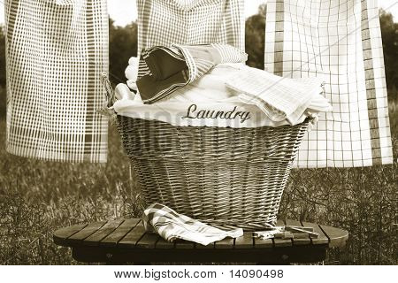 Laundry basket on rustic table with clothesline/ Sepia tone