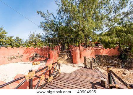 wooden pier leading to beautiful orange hotel on Turtles Island, Zanzibar