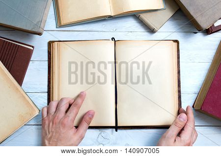 Old books with empty pages for your text and man's hand shows important place.