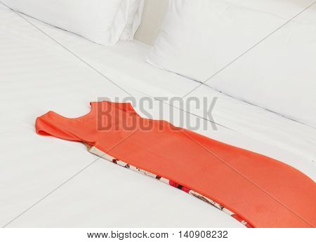 female pink coral  dress on the bed