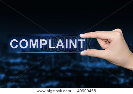 hand pushing complaint button on blurred blue background