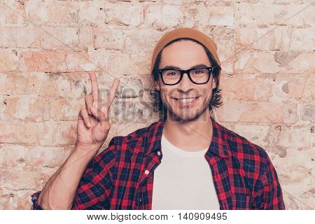 Hipster  Young Man Standing Near Brick Wall And Showing Two Fingers