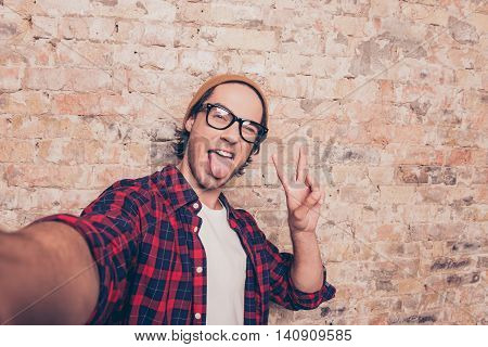 Funny Hipster Making Selfie Photo And Showing Tongue  Near Brick Wall