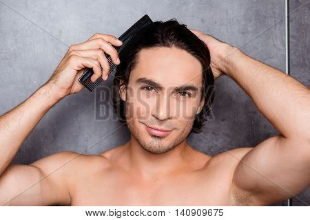 Portrait Of Sexy Handsome Young Man Combing His Hair
