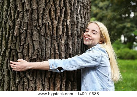 Young beautiful woman hugging a big tree in the park
