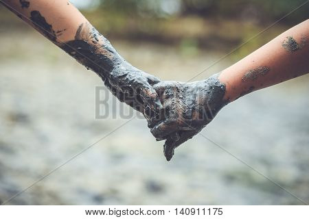 Children Hands Are Holding With Mud Clay. Help Concept. Retro And Vintage Style