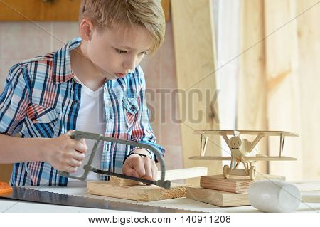 cute little boy  working with wood in  workshop