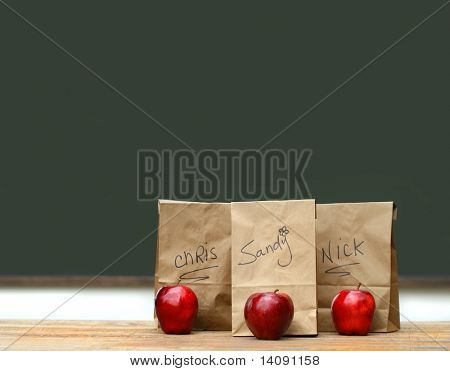 Lunch bags on desk with red apples in front of green chalkboard