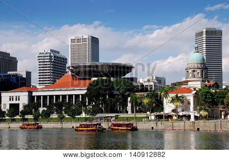 Singapore - December 28 2007: Singapore River touring boats the Singapore Parliament House (with orange roof) flying saucer shaped Supreme Sourt Building dome of the Old Supreme Court Building (green dome) and Raffles Landing Site