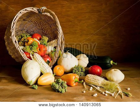 Overturned wicker basket full with various fresh vegetables on the table