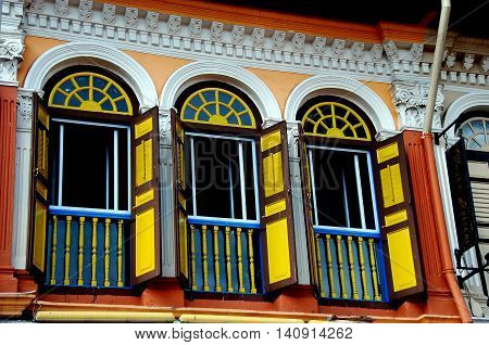 Singapore - December 17 2007: Restored early 20th century Chinese shop house with colourful windows on Bussorah Street in the Kampong Glam Arab district *