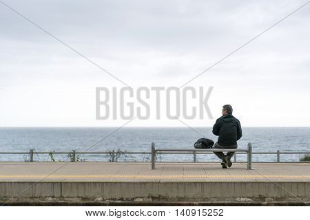 Corniglia Italy - Apr 8 2016: Unidentified backpacker old man tourist wait for train by the ocean with gloomy sky background looking at copy space at Corniglia train station Cinque Terre Italy