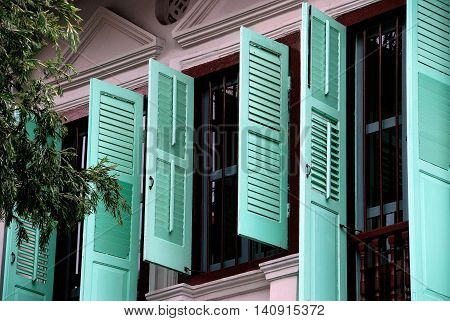 Singapore - December 15, 2007: A finely restored Peranakan home with mint green louvered wooden shutters in the Emerald Hill Conservation Area
