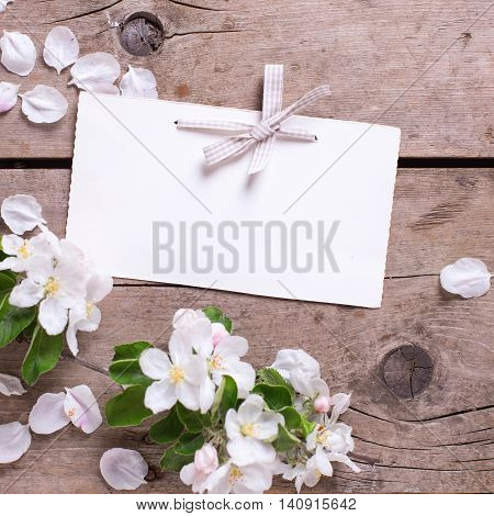 Empty tag and tender apple tree flowers on aged vintage wooden background. Selective focus is on tag. Place for text.