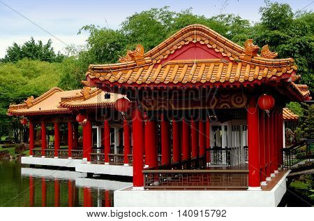 Singapore - December 27 2007: Lakeside viewing pavilions with orange tiled roofs and carved animal figures on the lagoon at the classical Chinese Garden