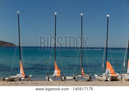 Colorful Sailboats And Motorboat, On A Tropical Beach