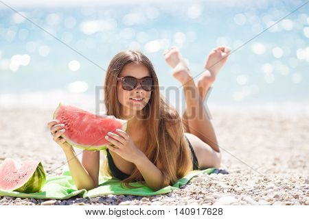 A beautiful young woman of Caucasian appearance with long straight blond hair,sun glasses ,laying on a beach towel on the green against the blue of the ocean wearing a black bikini,holding a slice of ripe watermelon with your legs crossed