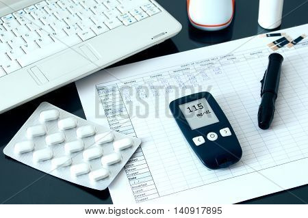 Blood glucose meter lying on a blood sugar diary. Conception of blood glucose testing.