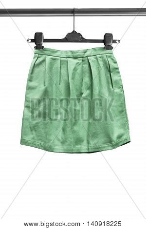 Green mini skirt on clothes rack isolated over white