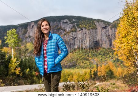 Autumn nature lifestyle happy Asian woman relaxing outdoors on camping travel park with mountain background. Hiking girl wearing blue down jacket enjoying fall season scenic landscape.
