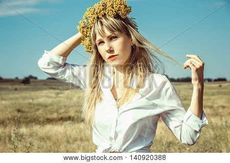 Photo of the Portrait beautiful young woman with blonde long hair and chaplet