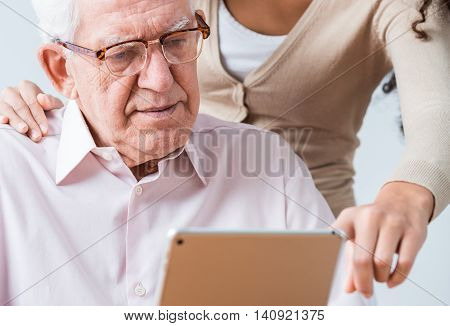 Woman Helping Elderly Man To Read Questionnaire