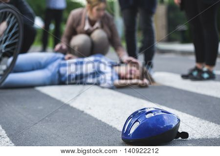 Place of an accident with onlookers standing around the young woman casualty