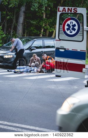 Emergency rescuer giving the first aid to the victim of an accident