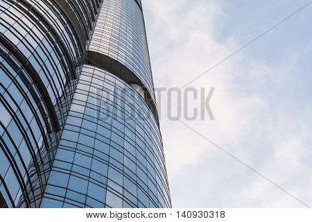 Glass windows pattern on the building with blue sky and white cloud in sunny day.