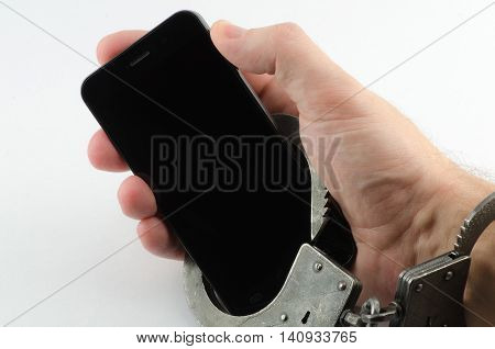 Hand with handcuffs chained to the phone